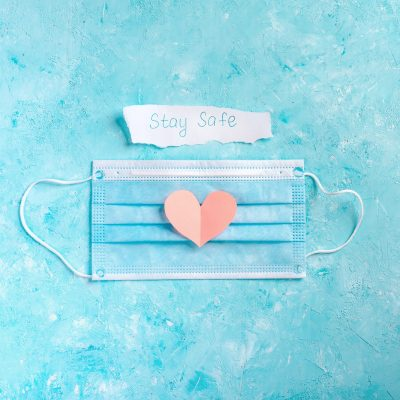 Facial mask with a sign stay safe and cut out pink heart shape on blue background.